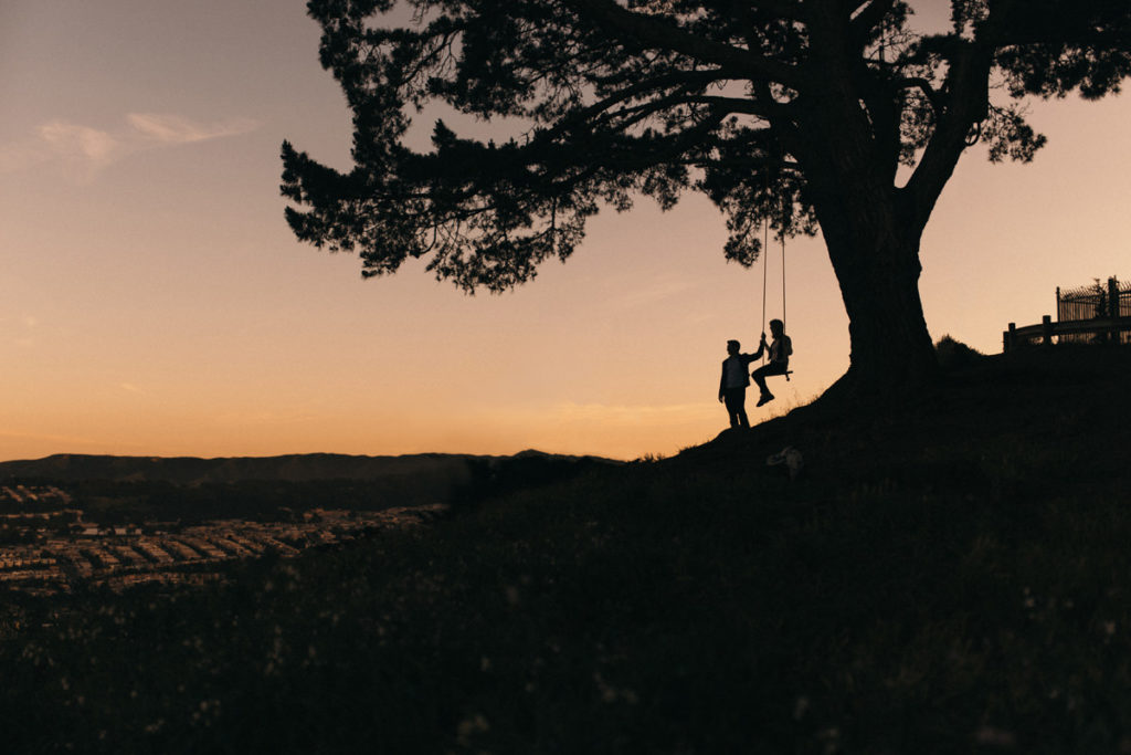 Beautiful sunset photograph at Bernal Heights swing in San Francisco, California, USA. Silhouettes against the golden sundown sky. Engagement couple session in Bay Area. Bernal Heights Park in San Francisco.