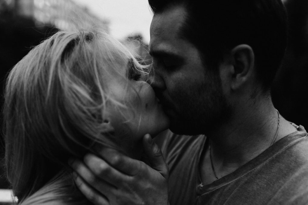 Emotional and intimate portrait of a couple kissing on the street. Intimate engagement photosession London. Free spirits, wild hearts, young couple kiss.