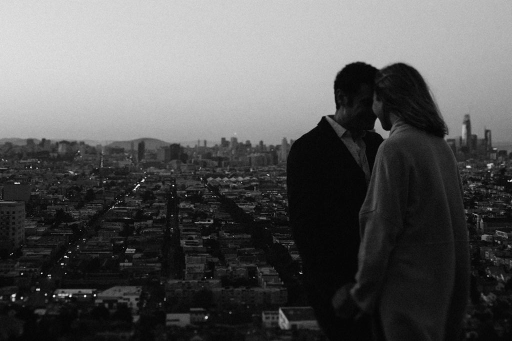 Black and white wedding photograph in San Francisco. Moody feel, sunset and city lights