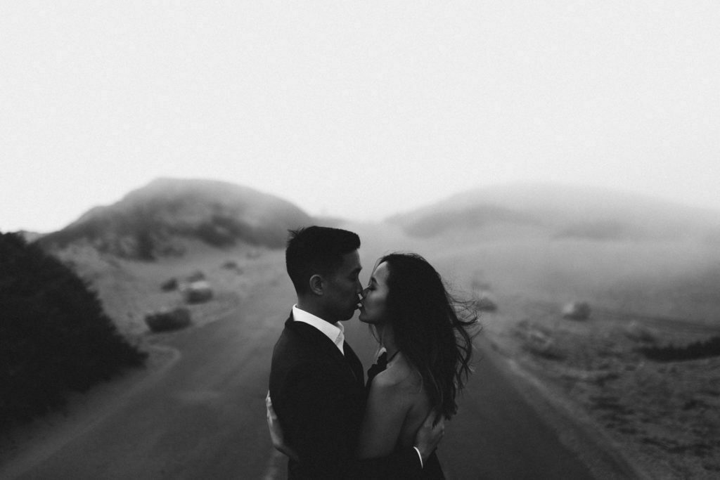 Romantic couple picture at foggy Point Reyes, California. Intimate after wedding photosession. Couple kissing in an embrace.