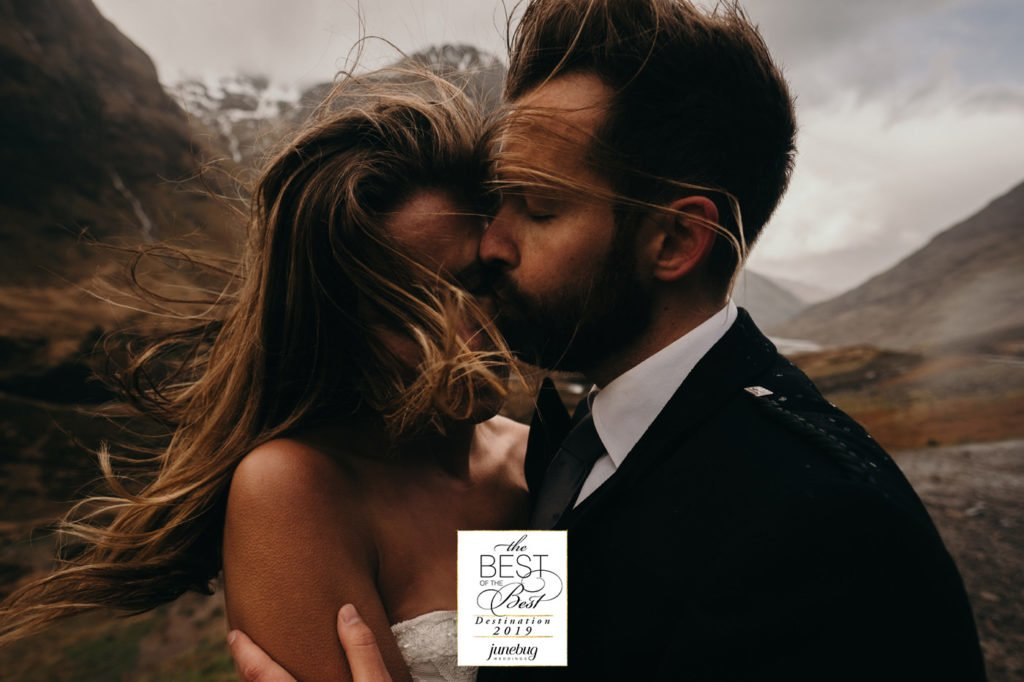 Best wedding and elopement photography by Junebug Weddings. Emotional kiss and embrace in Three Sisters Mountains, Glen Coe, Scotland, UK. After wedding photoshoot. Elopement in highlands in Scotland.