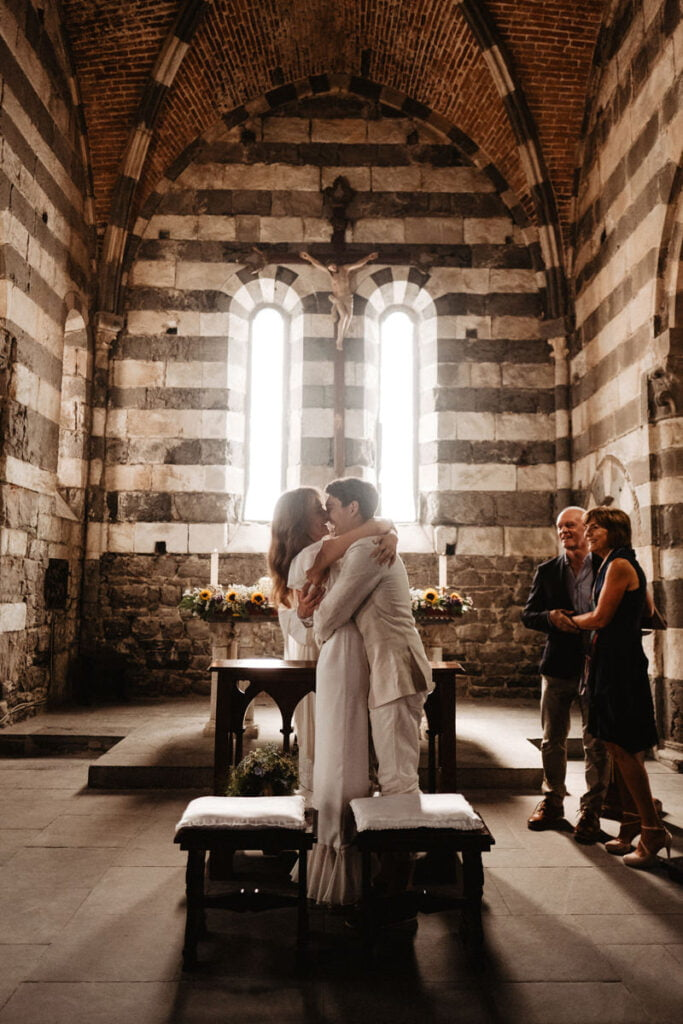 Romantic wedding in medieval church san pietro in portovenere. Getting married in Roman Catholic Saint Peter's church. Couple lighting a candle in a medieval church in Italy. Romantic wedding ceremony.
